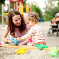 woman and toddler playing in sandbox